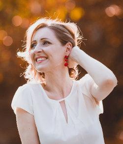 Kobieta w białej bluzce odgarnia włosy