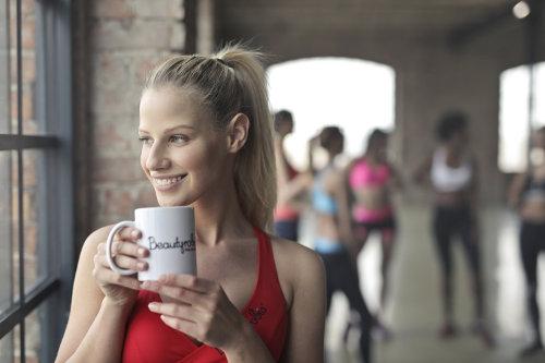 Kobieta po gimnastyce pije kawę