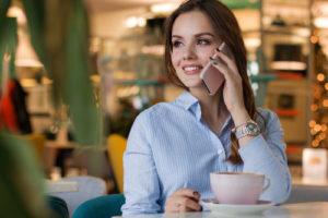 Kobieta w kawiarni rozmawia przez telefon komórkowy