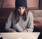 Kobieta z słuchawkami na uszach siedzi przy laptopie